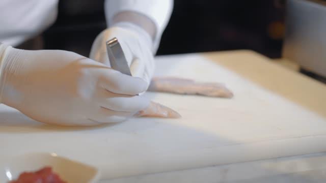 Unrecognized cook in rubber gloves prepare raw fish fillet over cutting board.