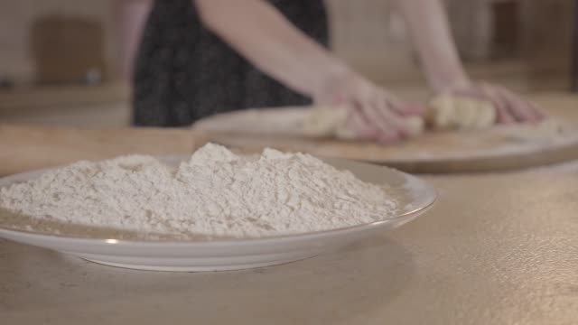 vidéos et rushes de fille non reconnue roule la pâte sur la table de cuisine fermer. - rouge à lèvres rouge