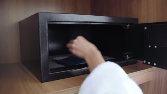 Unrecognized woman with red nails in her dressing gown puts her passport and money in the hotel safe. Enter security code and access Unrecognized woman with red nails in her dressing gown puts her passport and money in the hotel safe. Enter security code and access. passport stock videos & royalty-free footage