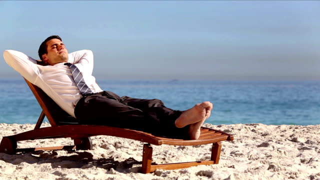 Unstressed businessman relaxing on the beach video