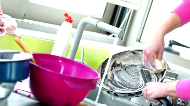 Untidy Kitchen slow motion. Closeup of unrecognizable woman doing dishes with lots of dirty plates and pots waiting aside. Slow motion, 4 times slowed down. cooking pan stock videos & royalty-free footage