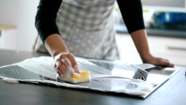 Untidy Kitchen Closeup of unrecognizable woman cleaning glass ceramic stove top with a detergent and a soft cleaning sponge. 4k cooking pan stock videos & royalty-free footage