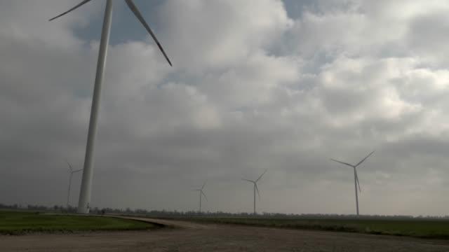 Geradores de energia eólica sem título em um campo de primavera - vídeo