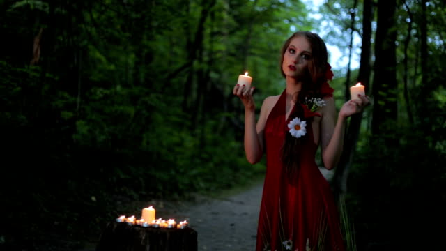 unusual girl with creative make-up holding two burning candles in dark forest - gothic fashion stock videos and b-roll footage