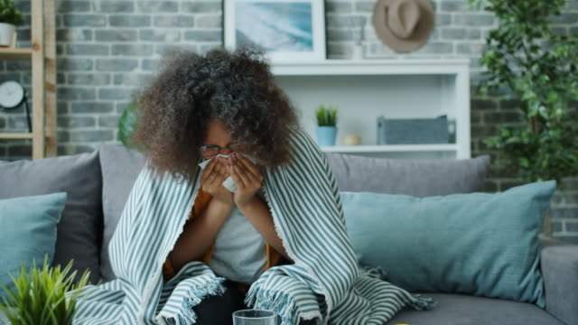 vídeos de stock e filmes b-roll de unwell teenage girl holding paper tissue and sneezing feeling bad at home alone - doença