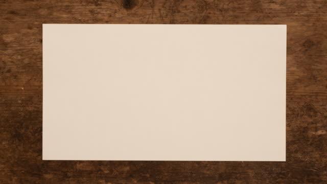 開梱と木製の背景を一枚の紙をラップします。白紙の折り重なりと開き、木製パネルに注意してください。 - 材木点の映像素材/bロール