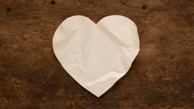 Unwrapping and wrapping heart shaped paper note on wooden background. Folding and unfolding of blank paper heart.