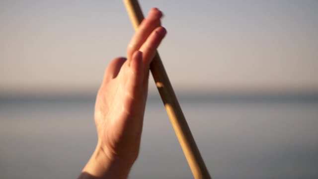 Up close view of drumsticks spinning while panning around the drum set. Man holding Chopsticks. Slowmotion Up close view of drumsticks spinning while panning around the drum set. Man holding Chopsticks. Slowmotion. stick plant part stock videos & royalty-free footage