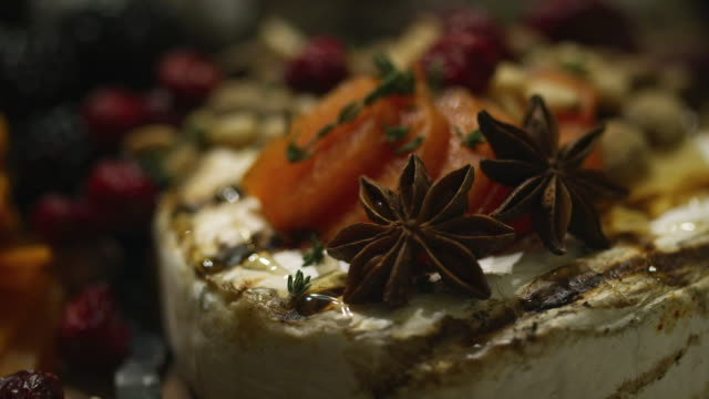 vídeos de stock e filmes b-roll de up-close shot of baked brie cheese, dried apricots, thyme, and star anise on an appetizer plate at an indoor celebration/party - assado no forno