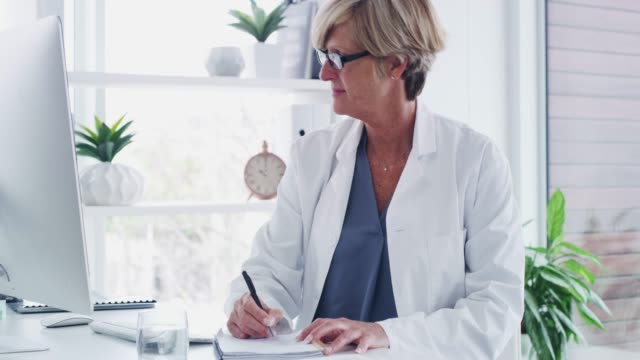 Updating her patients' medical records 4k video footage of a mature doctor writing notes while working on a computer in her office female doctor stock videos & royalty-free footage