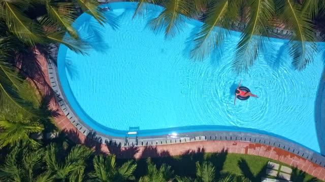 övre genom palm grenar på flicka paddling på ring - inflatable ring bildbanksvideor och videomaterial från bakom kulisserna
