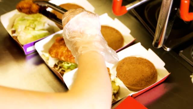 upper view cooker makes and packs tasty fresh hamburgers - rękawiczka filmów i materiałów b-roll