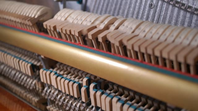 Upright Piano Mechanism Hammers Striking Strings When Song is Played by Musician