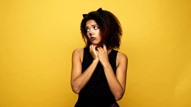 Upset african lady cat becoming cheerful and looking camera isolated ovr yellow video