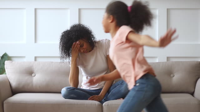 Upset african single mother feeling stressed about active noisy children