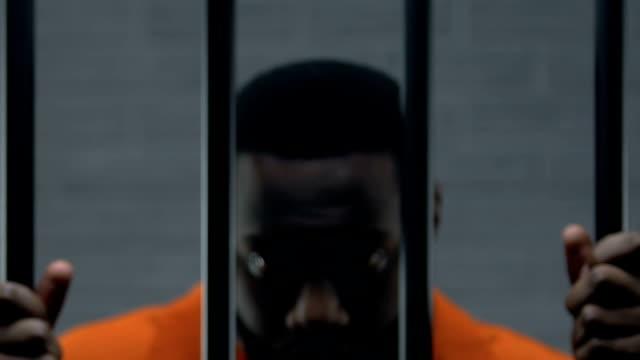 upprörd afro-amerikansk fånge hålla barer i cellen och titta på kamera, skyldig - fånga bildbanksvideor och videomaterial från bakom kulisserna