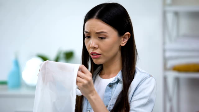 verärgert asiatische hausfrau zeigt kaffee fleck auf shirt vor der kamera, wäscheservice - schmutzfleck stock-videos und b-roll-filmmaterial