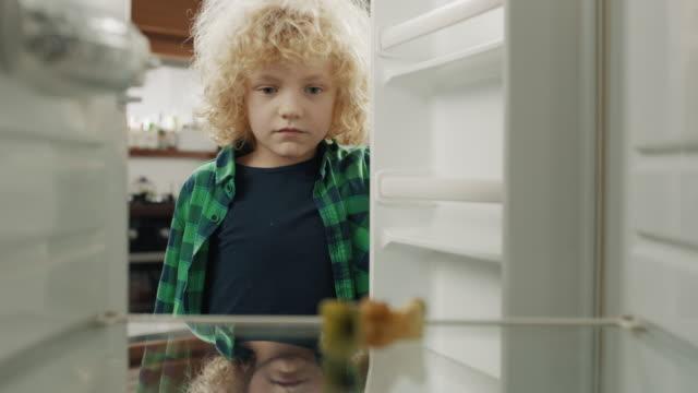 расстроенный мальчик смотрит на пустой холодильник - голодный стоковые видео и кадры b-roll