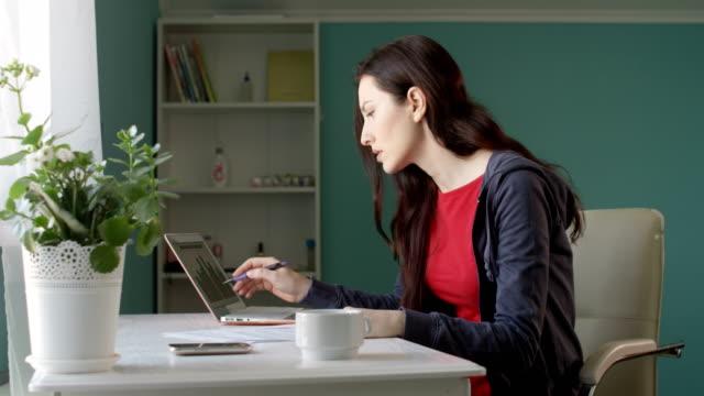 Verärgert Brünette Kleinunternehmer betonte, über schlechten Verkaufszahlen am Home Office Schreibtisch arbeiten am Notebook und Papiere zu werfen – Video
