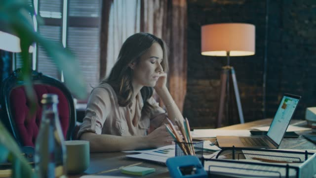 upset business woman using phone in cozy studio. depressed businesswoman - уютный стоковые видео и кадры b-roll