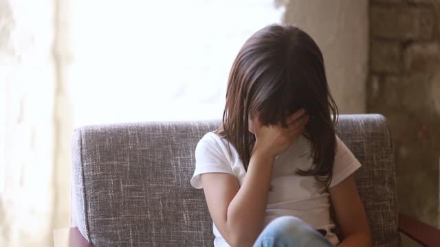 stockvideo's en b-roll-footage met boos kind meisje te kijken naar telefoon gevoel bang van pesten - kids online abuse