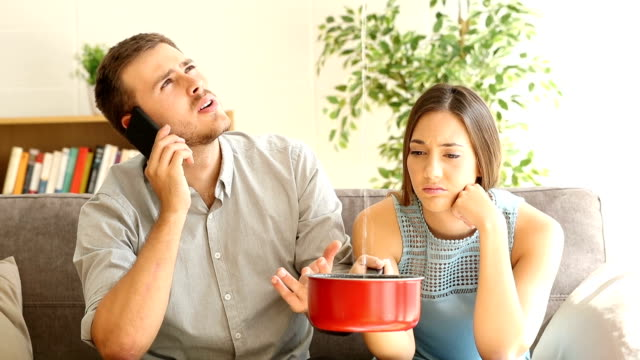Upset couple calling insurance watching home leaks