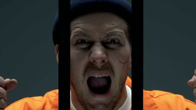 Upset criminal with scars on face holding prison bars, regretting about past Upset criminal with scars on face holding prison bars, regretting about past sentencing stock videos & royalty-free footage