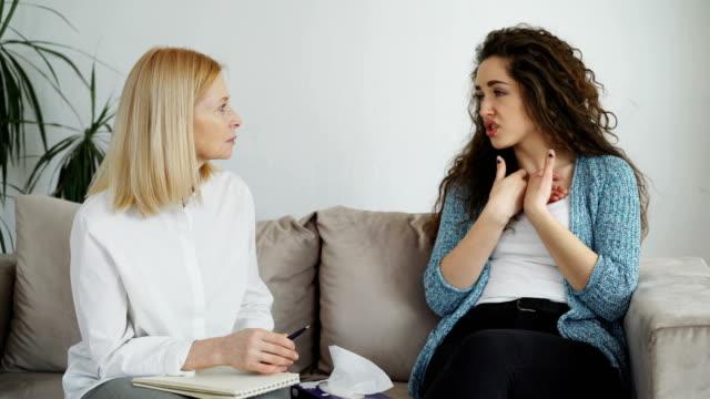 vídeos y material grabado en eventos de stock de chica llora molesta tener consulta con profesional psicólogo femenino que tejido papel destacó mujer en oficina de psicoterapeuta en el interior - profesional de salud mental