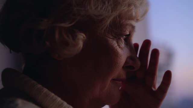 upprörd äldre lady torka tårar, gråt ensam nära fönster, ensamhet vid ålderdom - saknad känsla bildbanksvideor och videomaterial från bakom kulisserna