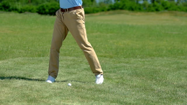 Upset golf player hitting ball and missing, bad position for hit, slow-motion