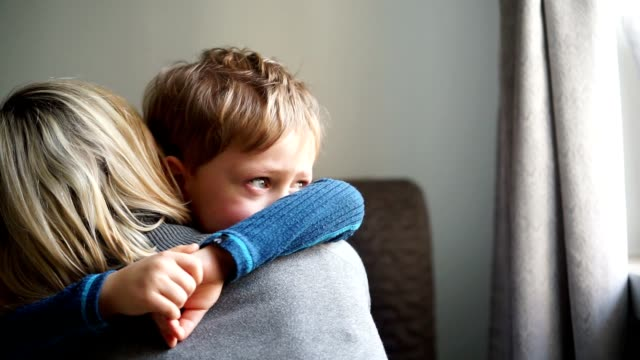 Upset little boy hugging his mother at home