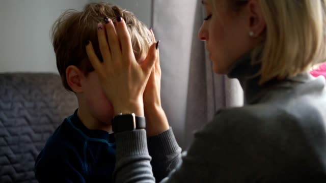 upset little boy hugging his mother at home - genitori video stock e b–roll