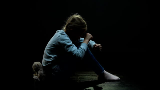 Upset little girl with teddy bear crying in dark abandoned room, loneliness Upset little girl with teddy bear crying in dark abandoned room, loneliness abandoned stock videos & royalty-free footage