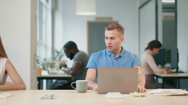 Upset man looking at laptop computer at workplace. Shocked man reading news