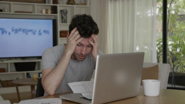 verärgerter mann arbeitet von zu hause aus und öffnet einen brief, der sehr besorgt aussieht, während er am laptop arbeitet - post it stock-videos und b-roll-filmmaterial