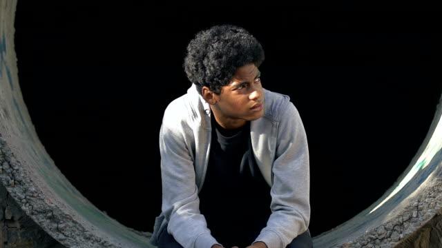 upprörd mixed-race tonårs pojke som sitter ensam i övergivna körfält, brist på kommunikation - saknad känsla bildbanksvideor och videomaterial från bakom kulisserna