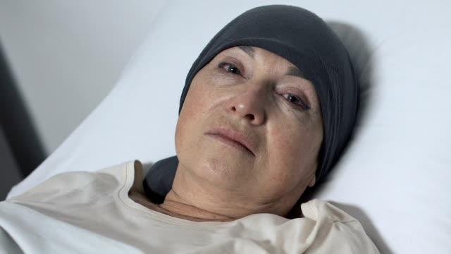 vídeos y material grabado en eventos de stock de molesto anciana en bufanda acostado en la cama y mirando a la cámara, paciente de quimioterapia - geriatría