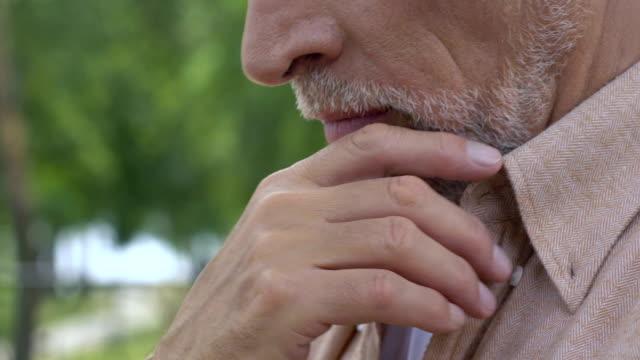 彼の顔に触れる動揺の古い男一人でベンチに座っていると、人生について考える ビデオ