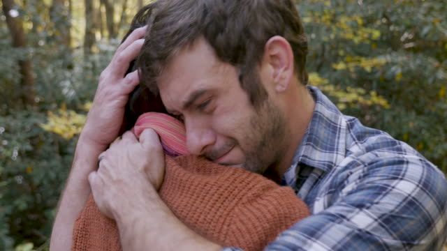 Upset sad man hugging a woman after getting bad news outdoors Upset sad man hugging a woman after getting bad news or mourning the loss of someone while outdoors at a park comfort stock videos & royalty-free footage
