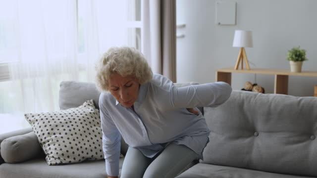 verärgerte seniorin fühlen sich zurück schmerzen aufstehen vom sofa - muskulös stock-videos und b-roll-filmmaterial
