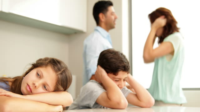 Upset siblings covering ears while their parents fight video