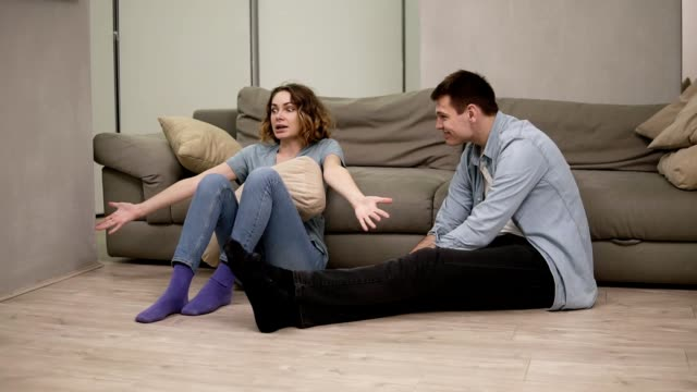 Upset stressed young caucasian girl feeling offended by boyfriend or husband while he is smiling - arguing shouting, jealousy. Sitting on the floor. Small quarrel in marriage relationship video