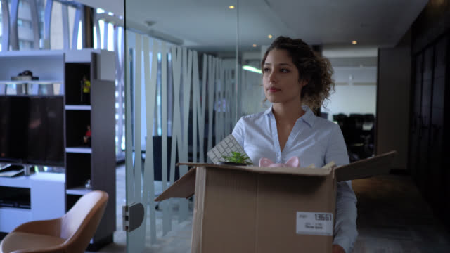 Upset woman carrying a box with her office things after a company downsize