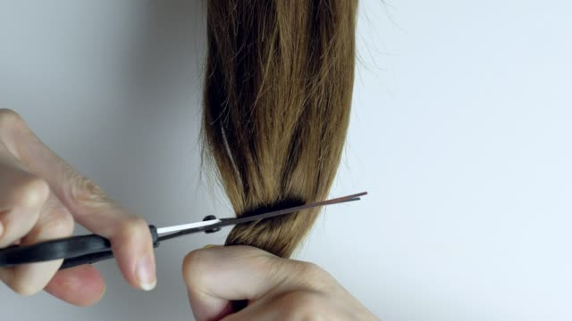 Upset woman cuts her long straight hair with scissors Close up - Unrecognizable upset woman cuts her long straight hair with scissors. human hair stock videos & royalty-free footage