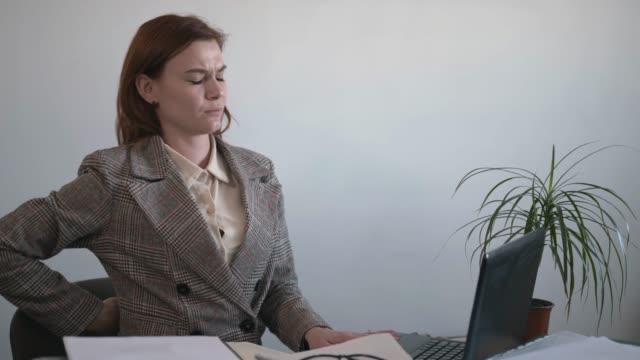 upprörd kvinna känner ryggont medan massera muskelsmärta, ledsen kvinnlig anställd lider av smärta i nedre ryggen sitter i fel position sitter, arbetar på datorn i tjänst, begreppet radikulit - människorygg bildbanksvideor och videomaterial från bakom kulisserna