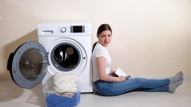 verärgerte frau sitzt auf dem boden in der nähe von waschmaschine im zimmer - waschmaschine wand stock-videos und b-roll-filmmaterial