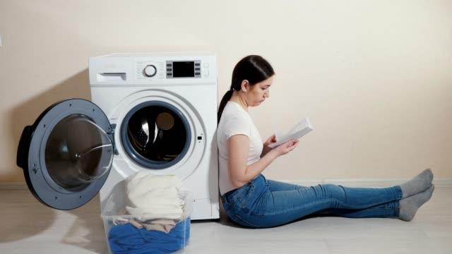 verärgert eiterin mit schmutziger wäsche in derbox und handbuch in den händen sitzt auf dem boden - waschmaschine wand stock-videos und b-roll-filmmaterial