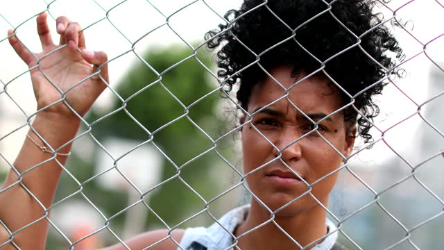 Upset young black woman leaning on metal fence