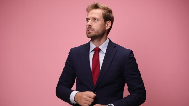 upset young businessman looking down and checking time, being late, face palming, looking up and nodding, disapproving on pink background