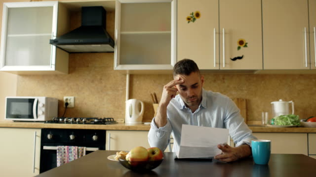 vídeos de stock e filmes b-roll de upset young man reading letter with unpaid bill in the kitchen at home - mensagem